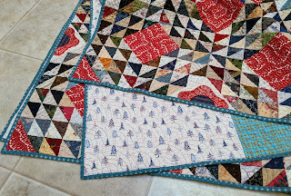 The folded quilt highlights the front, back, and blue binding