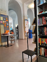 Open space with books filled shelves and colorful notice boards in public library