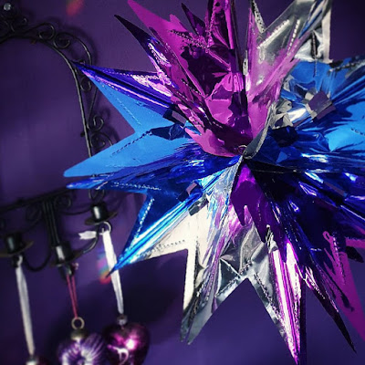 A foil star of alternating purple, silver and blue sections viewed from the upper right, looking down onto it, with a dark purple wall in the background and on the purple wall is the black metal frame of a former-mirror missing its glass - it is a black Gothic arch with swirling spirals and three candle-sconces on the bottom. Three glass hearts are hanging from the candle-sconces. The foil star is in focus, the black mirror frame isn't