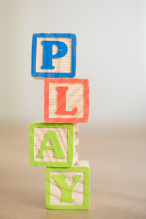 wooden blocks with letters spelling out the word PLAY