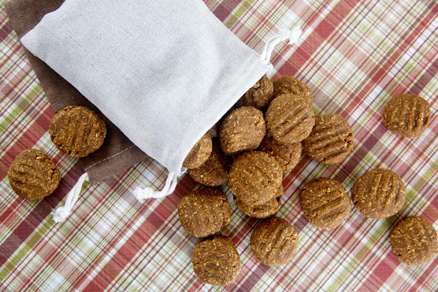 Homemade dog treats spilling out of a drawstring bag onto a plaid table cloth