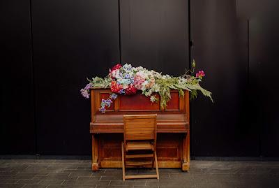Piano decorado con flores y una silla vacía delante del teclado