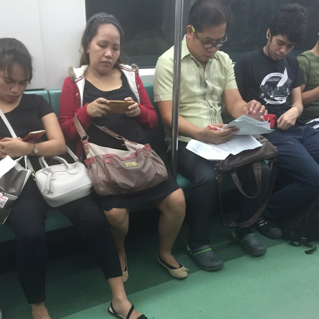 Netizens praise hardworking teacher seen checking papers even inside LRT
