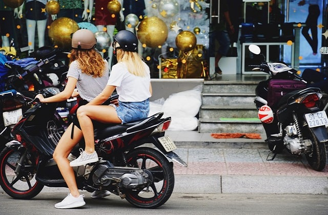 Two women on motorcycle with helmets
