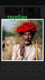 на голове мужчины одет тюрбан красного цвета с палкой в руках