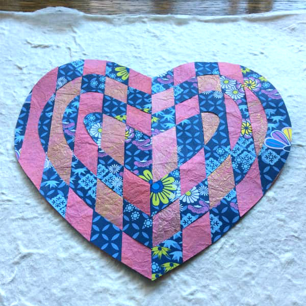 woven paper heart displayed on textured handmade paper