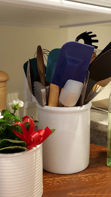 A kitchen crock full of kitchen tools.