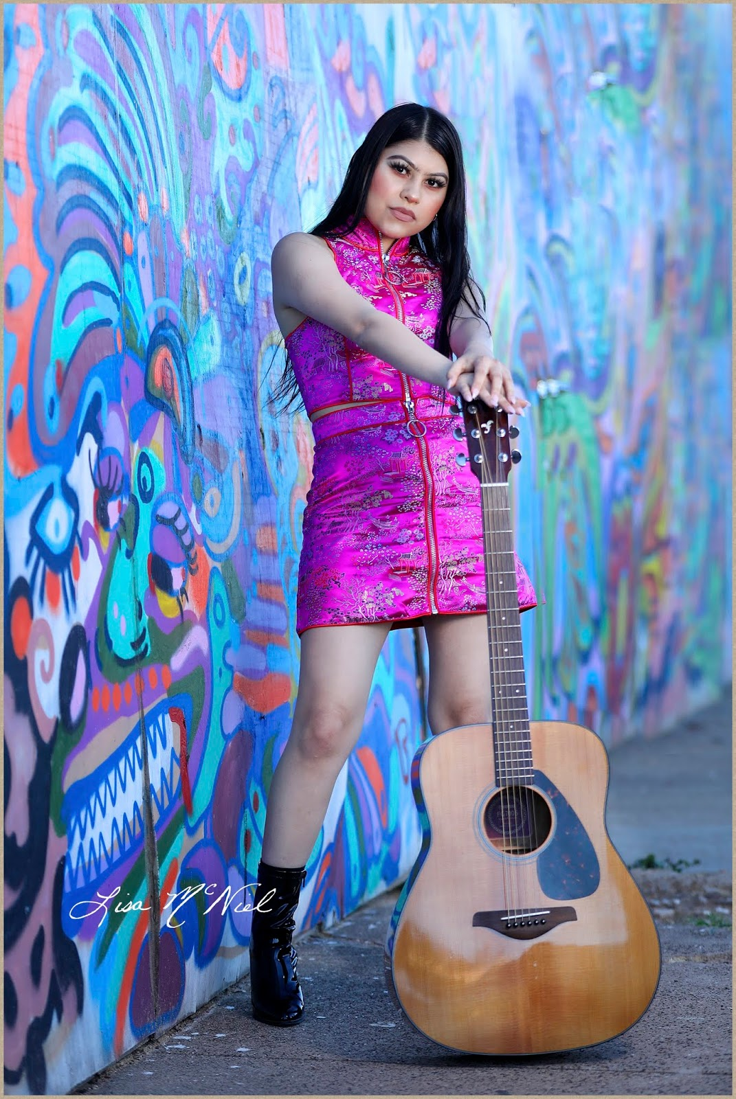 asian girl in pink dress with guitar by colorful graffiti wall