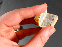 A hand holding a miniature book in Arabic.