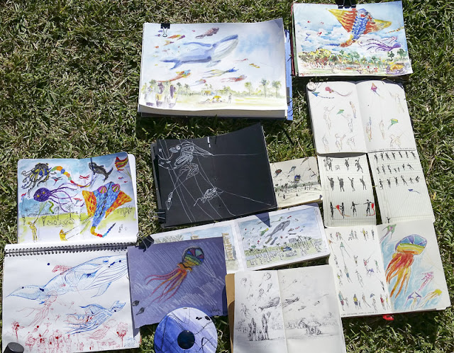a number of sketchbooks on the ground to compare and view everyone's sketches of colorful kites