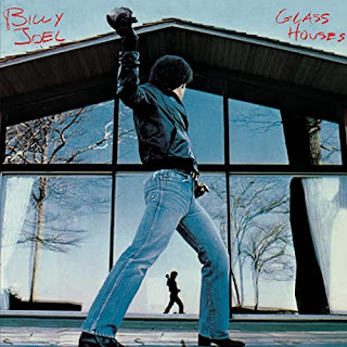 Billy Joel starting to throw a stone through a huge window
