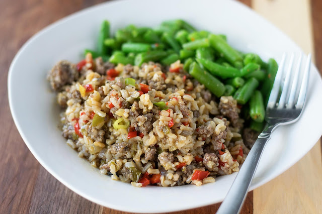 A white place with the Easy Dirty Rice Recipe, green beans, and a fork.