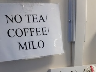 "A white laminated sign with large capital letters: ""NO TEA / COFFEE / MILO"""