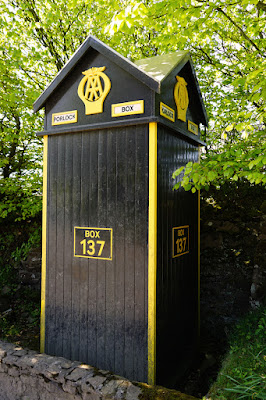 Photograph of a square, black wooden structure with yellow-painted edges, set behind a low wall with trees behind it. There are signs on it including an AA logo, 'PORLOCK HILL', and 'BOX 137'
