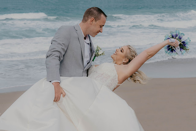 Groom dipping Bride on the beach with the ocean behind them