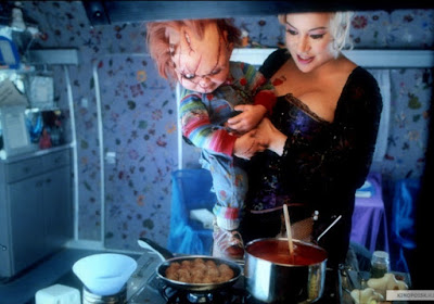 Jennifer Tilly holds Chucky while she's cooking in Bride of Chucky movie scene