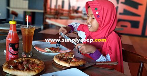 SERU  : Ini anak saya Tazkia sedang menikmati menu kesukaannya Pizza dengan pinggiran Keju.   Foto Asep Haryono