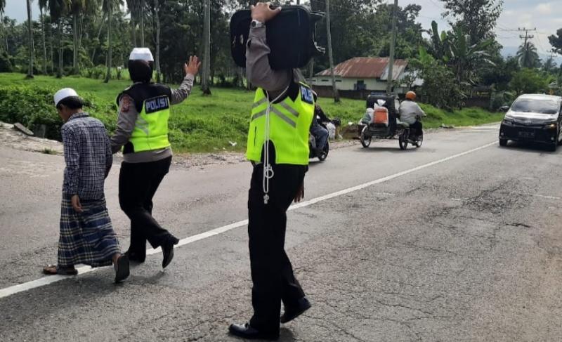 Personil Sat  Lantas Polres Madina Bantu Seorang Kakek Menyeberang Jalan