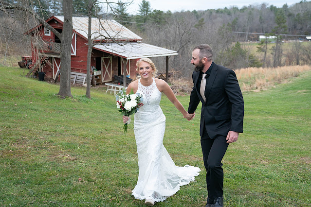 Bride and Groom strolling together on green field with red barn in the background Magnolia Farm Asheville Wedding Photography captured by Houghton Photography