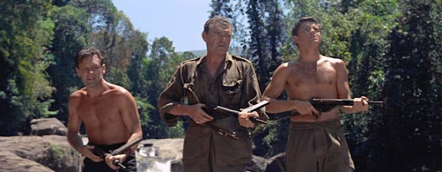 William Holden, Jack Hawkins and Geoffrey Horne holding machine guns