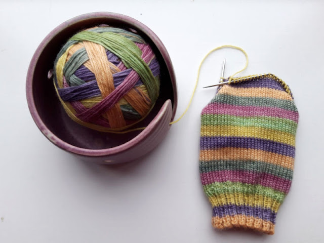 A ball of The Yarn Badger eco yarn sitting in a purple ceramic yarn bowl to the left, and a half-knitted sock showing the shades to the right