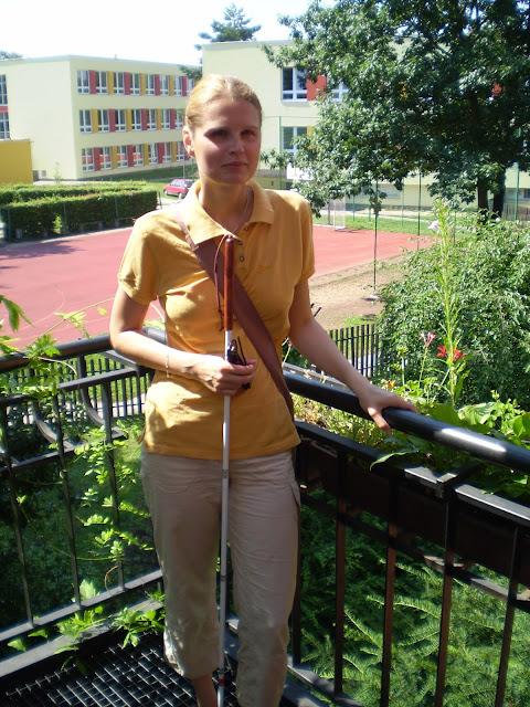 Linda stojí na terase, drží bílou hůl