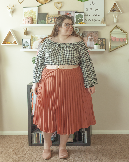 An outfit consisting of a black and white gingham blouse with long bell sleeves tucked into a pink pleated midi skirt and muted pink pointed toe mules.