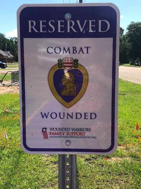 Sign says Reserved Combat Wounded Wounded Warriors Family Support. There is a picture of George Washington surrounded by a purple heart, and then by gold.