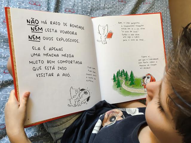 """Foto do Miguel lendo o livro infantil """"O gato, o cachorro, Chapeuzinho, os ovos explosivos, o lobo e o guarda-roupa da vovó"""", de Diane e Christyan Fox"""