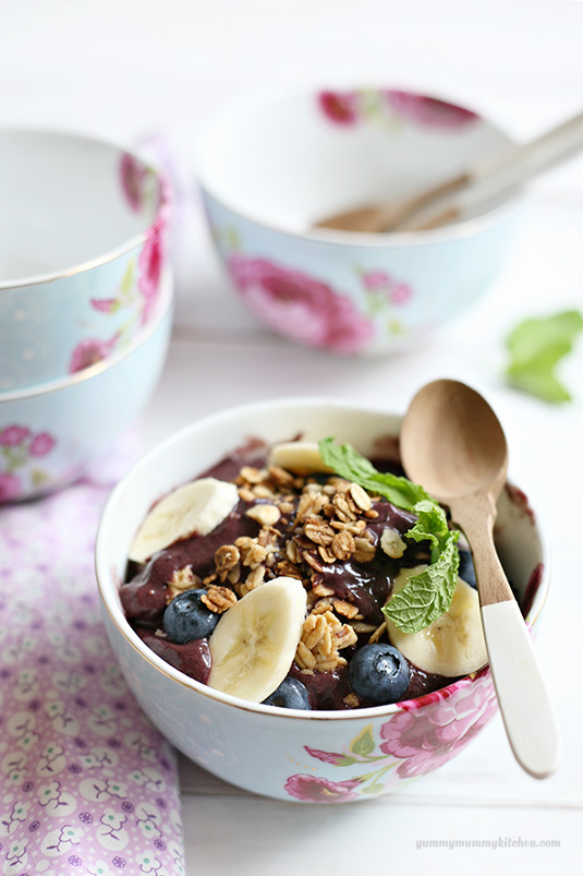 Beautiful acai breakfast bowl topped with berries, granola, and bananas.