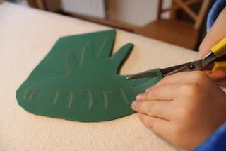 criança a cortar o desenho da mão, em goma eva