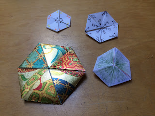 Hexahexaflexagons, one made of shiny wrapping paper
