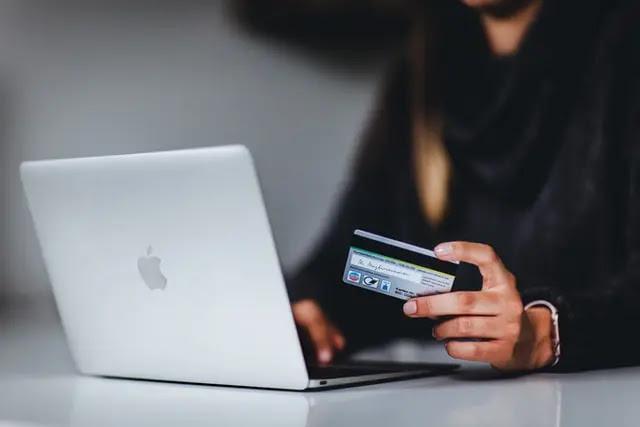 Mujer frente a laptop sosteniendo una tarjeta de crédito en su mano izquierda
