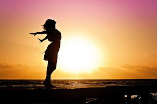 side view silhouette of girl with arms outstretched behind her in front of sunset