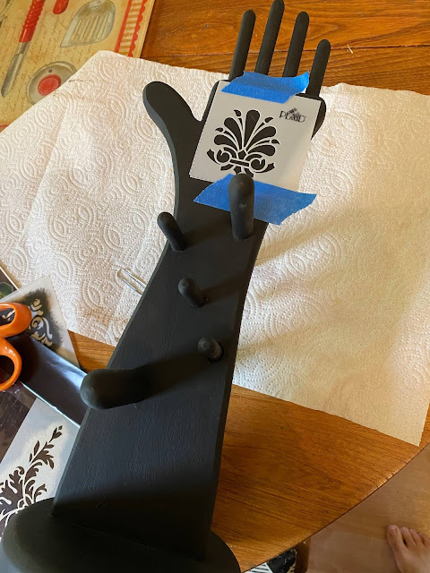 Photo of a black wooden hand shaped jewelry holder getting a stencil