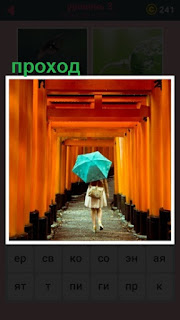 по центру прохода среди колонн идет девушка под зонтом