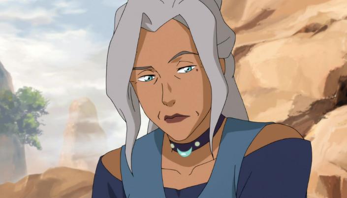 Imagem: a personagem Kya, uma mulher da tribo da água, com os cabelos brancos, magra, roupas em tons azuis, olhos azuis, um colar com um pingente de meia-lua e por trás dela uma paisagem montanhosa com névoa.