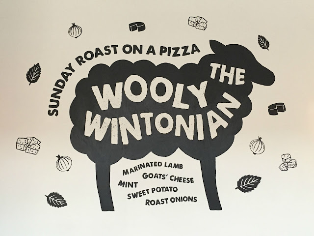 Sign writing on a wall advertising the Woolly Wintonian pizza