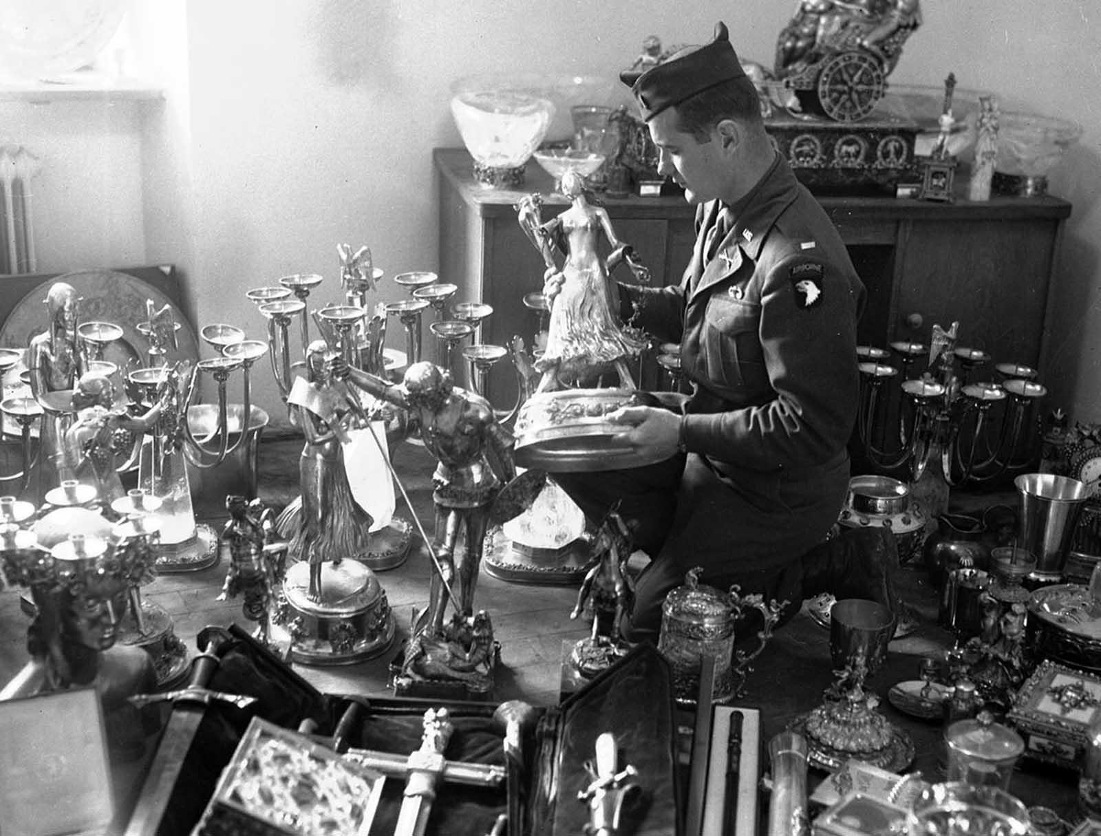 A U.S. soldier examines a solid gold statue, part of Hermann Goering's private loot, found by the 7th U.S. Army in a mountainside cave near Schonau am Konigssee, Germany, on May 25, 1945. The secret cave, the second found to date, also contained stolen priceless paintings from all over Europe.