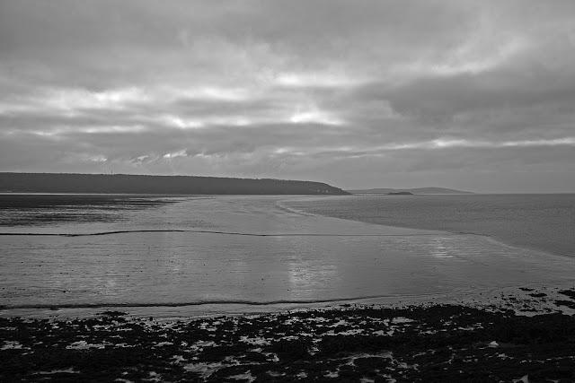 Long grey beach, stretching to horizon.