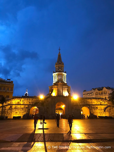 Pedestrians strolling in front of the lit main city gate of Cartagena de Indias, during the blue hour.