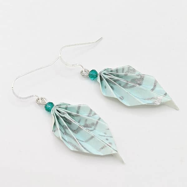 Pair of origami leaf earrings made with folded teal and silver chiyogami paper