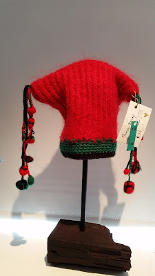 Red jester hat in rectangular style with green band. The hat corners are finished with plaited tassels and felted balls on the ends.