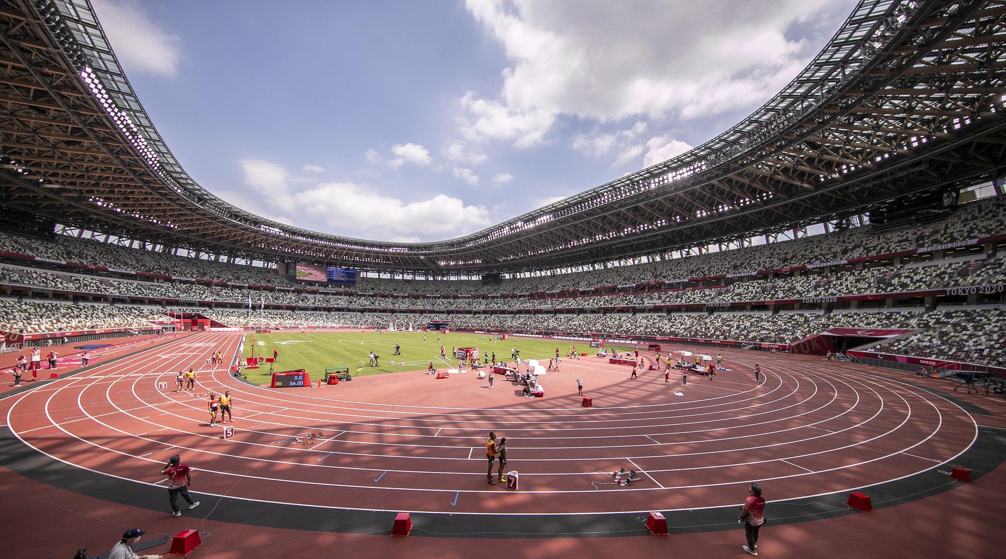Estádio Olímpico de Tóquio com algumas atletas cegas e seus guias se preparando para correr na pista
