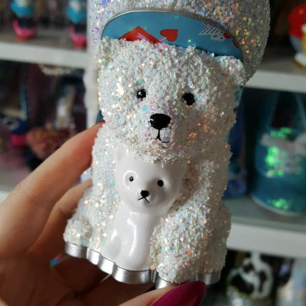 close up of white glitter polar bear and white cub heel of shoe in hand with shoes in background