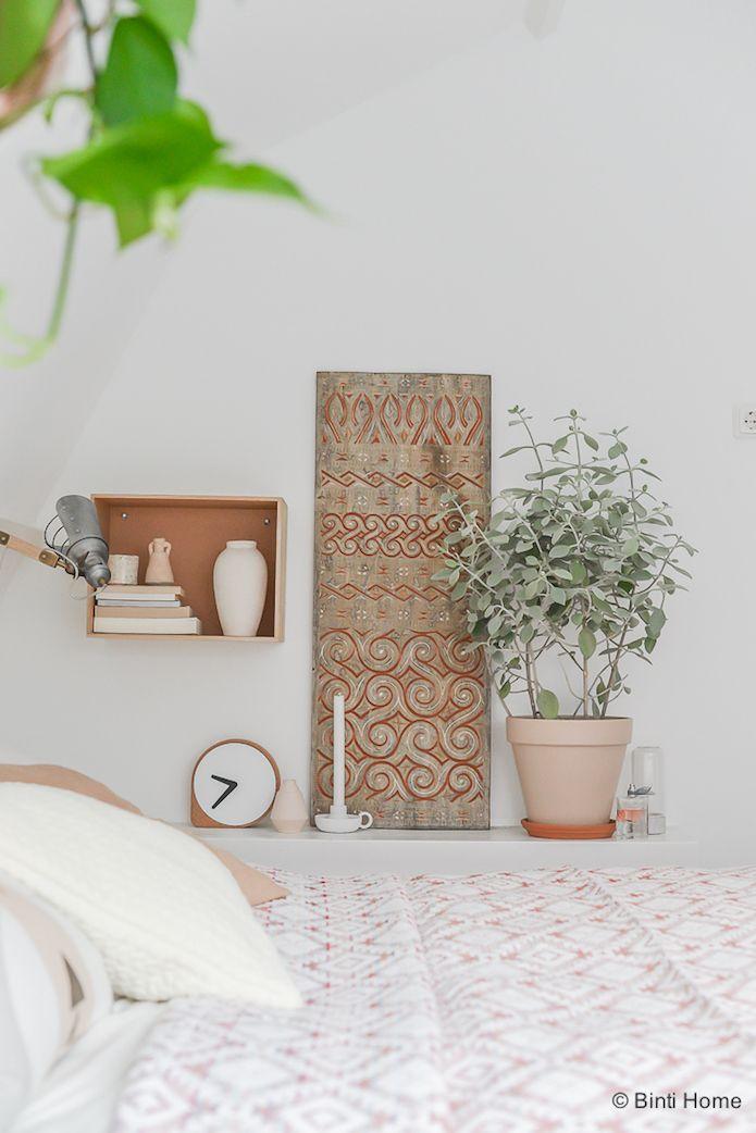 detalle de la cómoda de poca altura en un dormitorio. caja de madera, plantas, tapices.