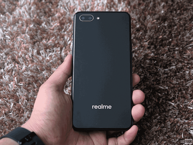 The back has a glass like material with just the Realme brand and the cameras