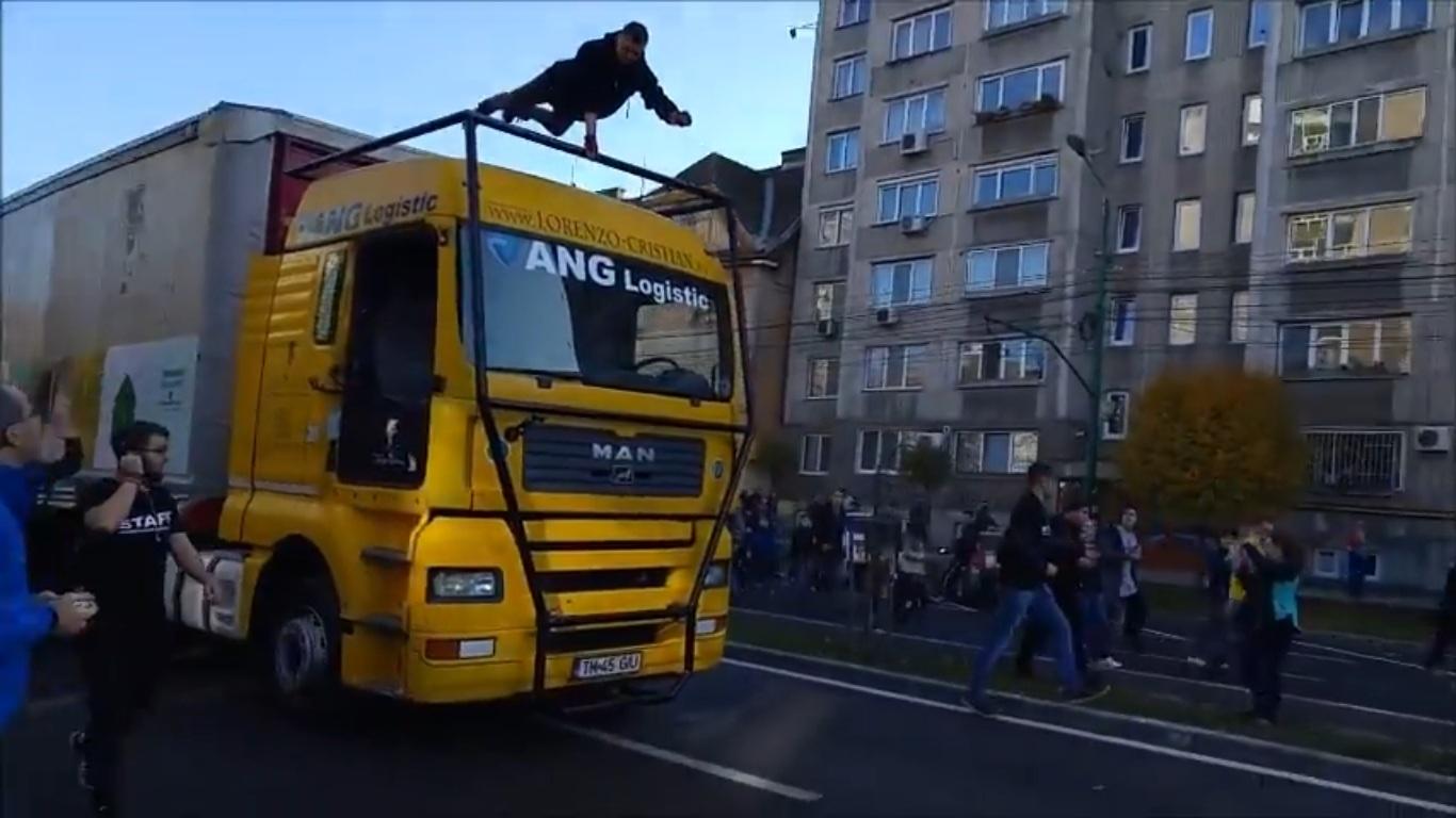 """Magicianul Lorenzo-Cristian a levitat și a condus un TIR la Timișoara prins de un suport special, atașată pe cabina autotrenului inscriptionat """"ANG Logistic""""."""