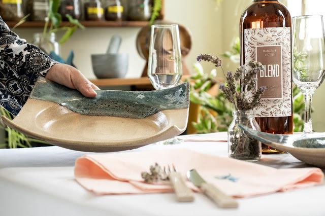 Prato de Cerâmica sendo colocado na mesa por mão feminina