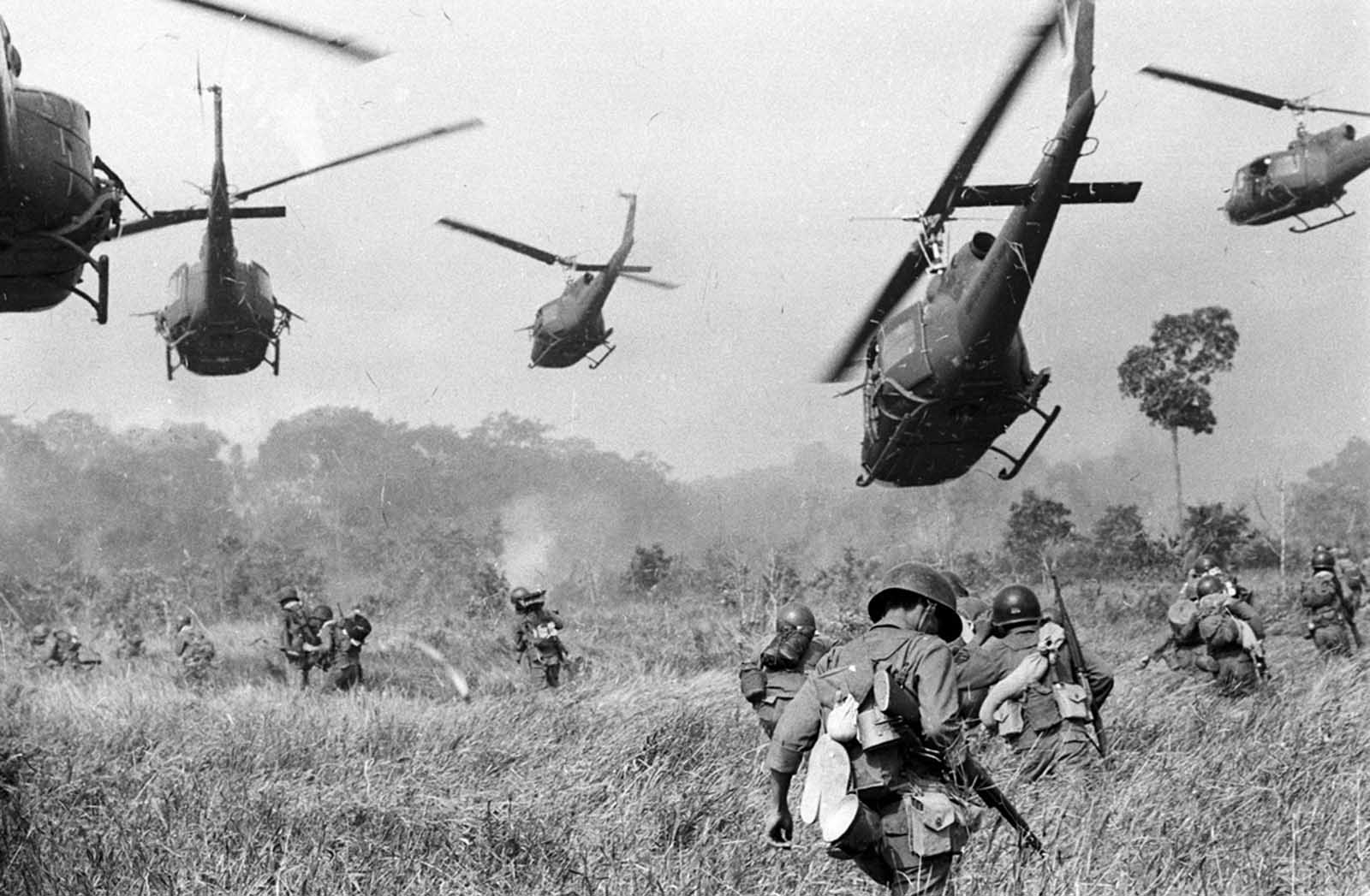 Hovering U.S. Army helicopters pour machine gun fire into a tree line to cover the advance of South Vietnamese ground troops in an attack on a Viet Cong ...